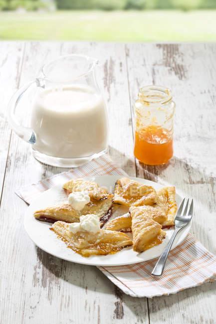 Panzerotti di pasta sfoglia con marmellata di albicocche e panna montata — Foto stock