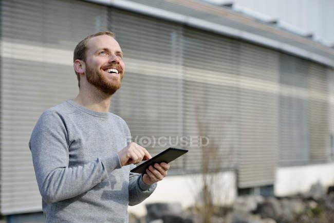 Portrait de jeune homme heureux avec mini tablette — Photo de stock