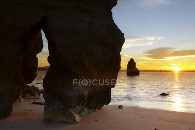 Скалы на пляже в лучах заката — стоковое фото