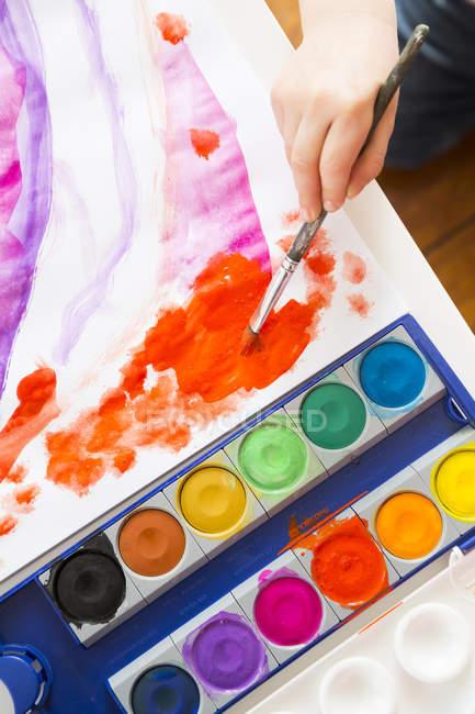 Vista ritagliata della pittura bambino con acquerelli — Foto stock