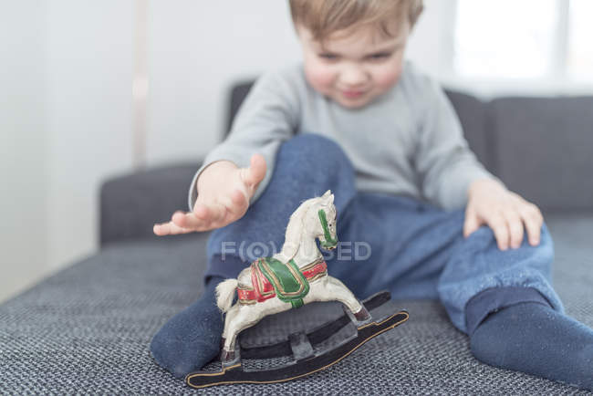 Little boy playing with wooden rocking horse — Stock Photo