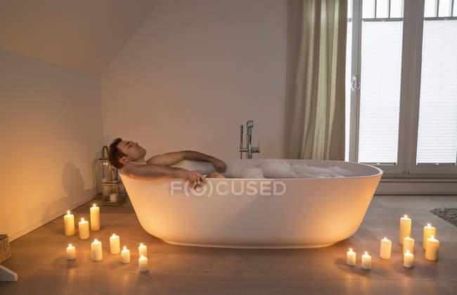 Vasca Da Bagno Romantica Con Candele : Uomo che si distende in vasca da bagno con candele accese arround