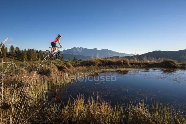 Bicicleta de montaña de Austria Altenmarkt-Zauchensee, mujer joven del montar a caballo al amanecer - foto de stock