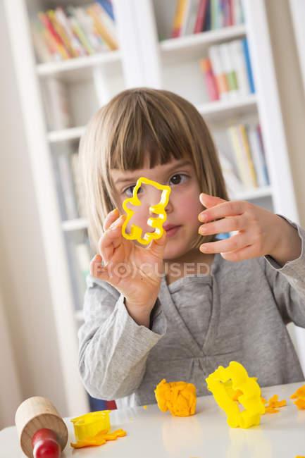 Ritratto di bambina con taglierina gialla in mano — Foto stock