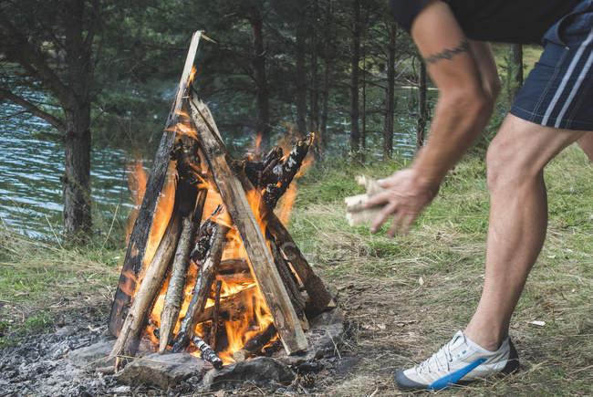 Un homme allume un feu sur une prairie — Photo de stock