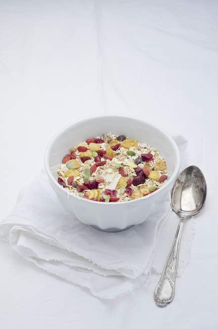 Bowl of homemade muesli with cereals, berries, quinoa grains and coconut flakes on white cloth — Stock Photo