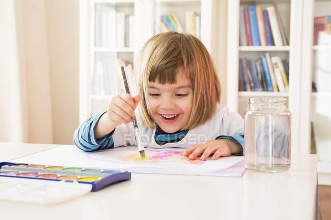 Portrait of smiling little girl painting with watercolours — Stock Photo