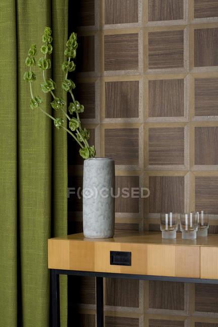 Sideboard mit Brille und Blume Vase vor hölzerne Wandverkleidung — Stockfoto
