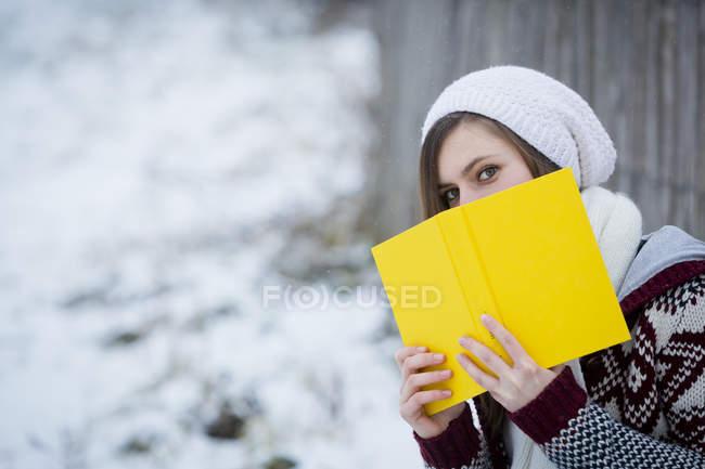 Молодая женщина прячется за желтой книгой — стоковое фото