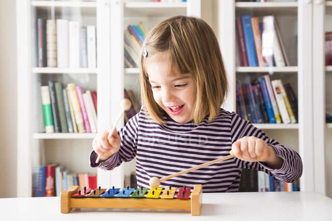 Portrait de heureuse petite fille jouant xylophone — Photo de stock