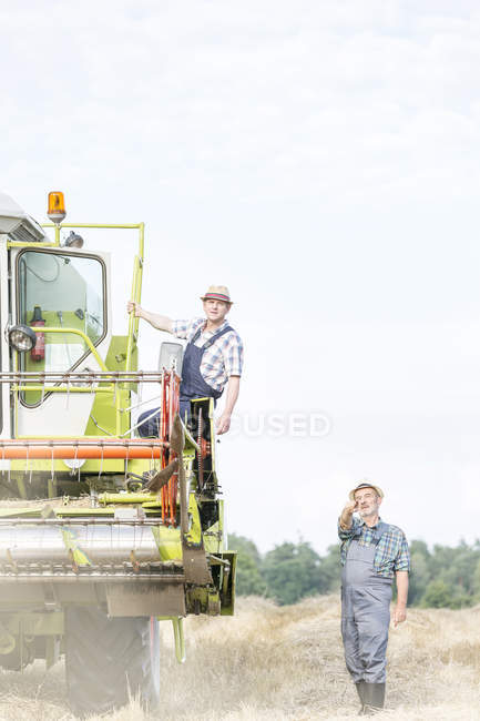 Two farmers with combine harvester on field — Stock Photo