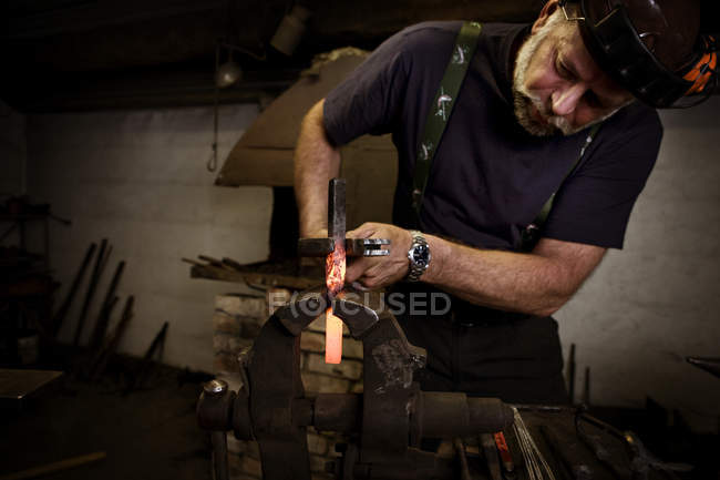 Blacksmith at work with incandescent metal element — Stock Photo