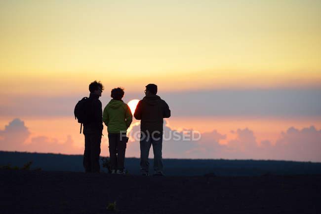 США, Гавайи, Большой остров, Национальный парк Вулканы, трое людей смотрят закат в Килауэа Ики — стоковое фото