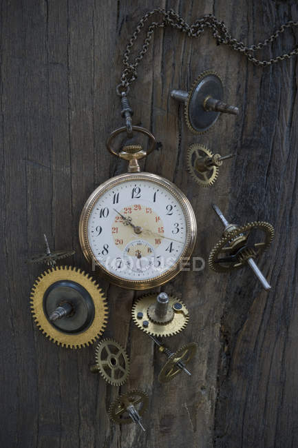 Old pocket watch and cogwheels on dark wood — Stock Photo