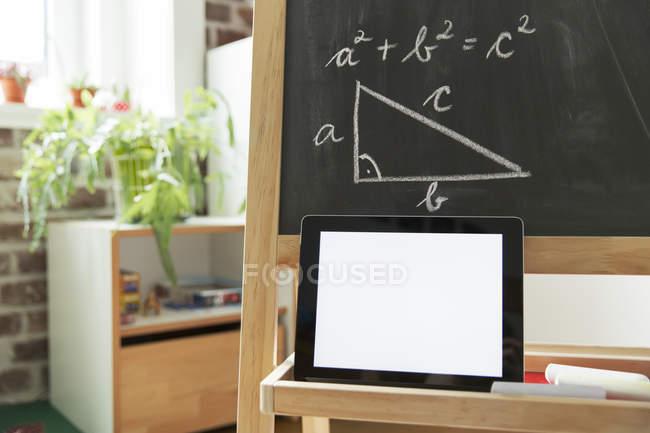 Tablet ordenador apoyado en pizarra en la habitación de los niños - foto de stock