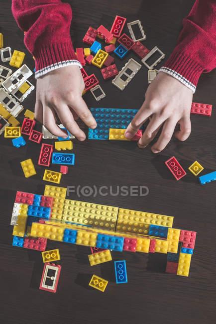 Kinderhände spielen mit Bausteinen auf einem Tisch — Stockfoto