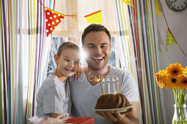 Отец и сын с праздничным тортом — стоковое фото
