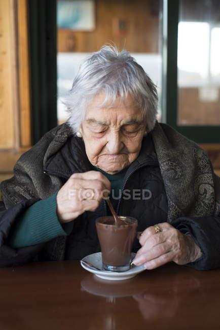 Vieille femme buvant du chocolat chaud au café — Photo de stock