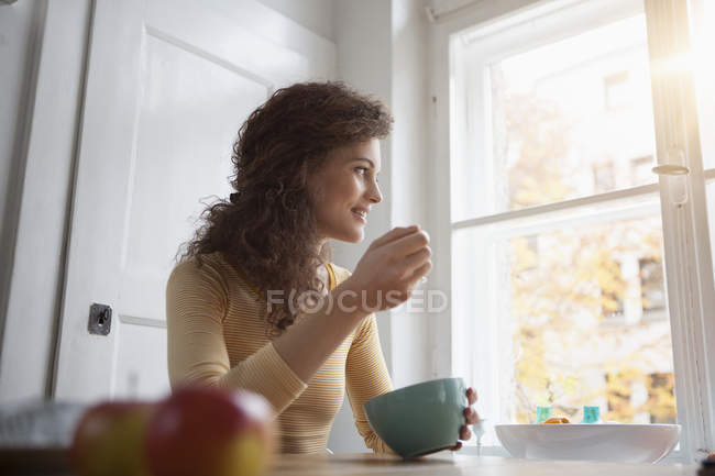 Молодая женщина на таблице еды из зерновых миски — стоковое фото