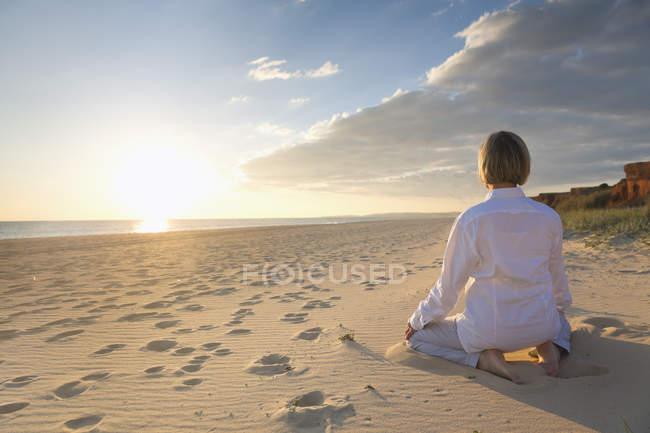 Португалия, Алгарве, женщина, занимающаяся йогой на пляже на закате — стоковое фото