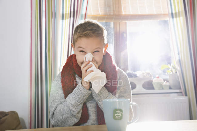 Boy sitting in the kitchen blowing his nose — Stock Photo