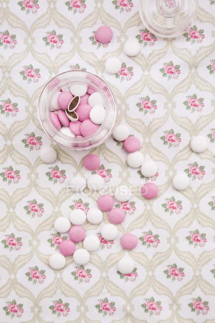 Rosa und weiße Schokolinsen auf floral gemusterten Stoff Glas — Stockfoto