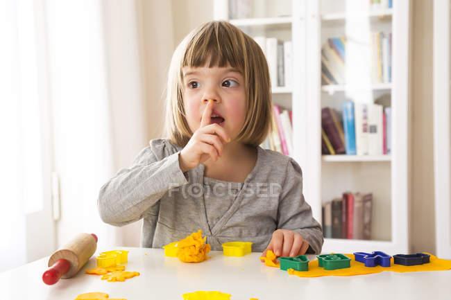 Kleines Mädchen spielt mit gelber Modelliermasse — Stockfoto
