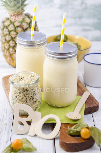 Pineapple smoothies to go with physalis and hempseeds — Stock Photo