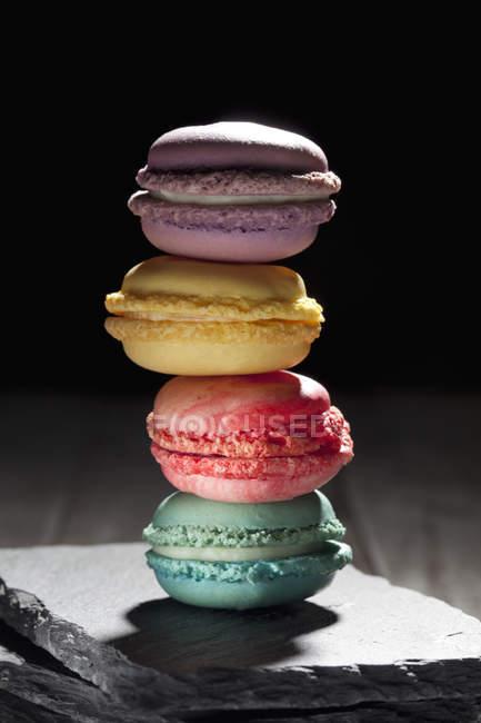 Stapel von vier verschiedenen Macarons auf Schiefer — Stockfoto