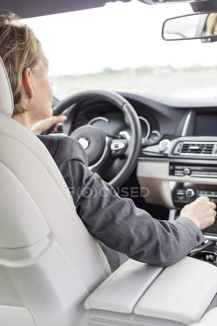 Rear view of businesswoman driving car — Stock Photo