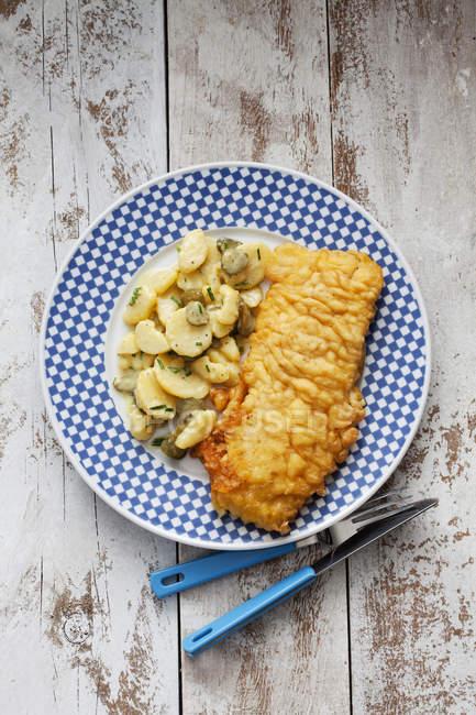 Блюдо жареная Сайда и картофельным салатом в пластину на потертом древесины — стоковое фото