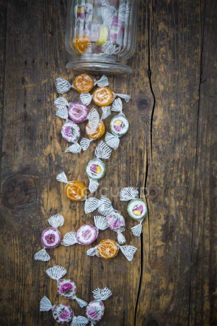 Frasco de doces e doces em madeira escura — Fotografia de Stock