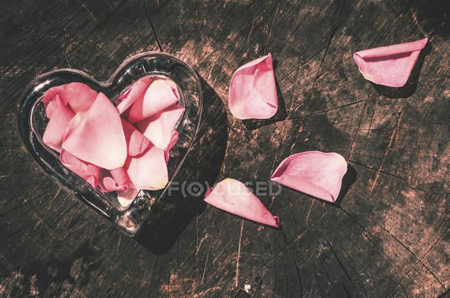 Сердцевидное стекло и лепестки роз на темном дереве — стоковое фото