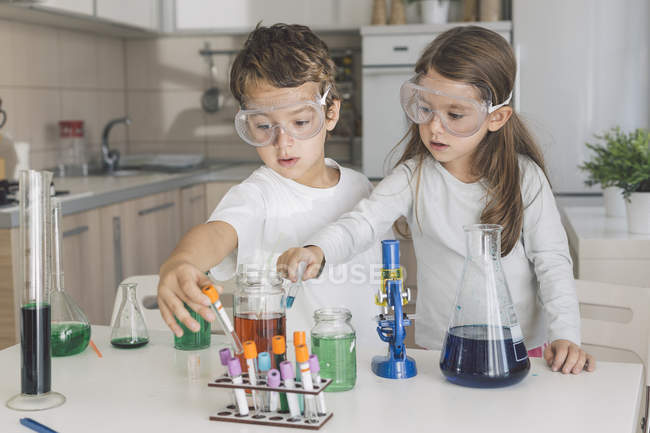 Boy and girl playing science experiments at home — Stock Photo