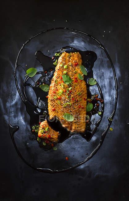 Lachs mit Paprika, rote Chili, schwarzer Sesam, Frühling Zwiebeln, Paprika, Kräuter, Öl und Marinade auf schwarze Oberfläche — Stockfoto