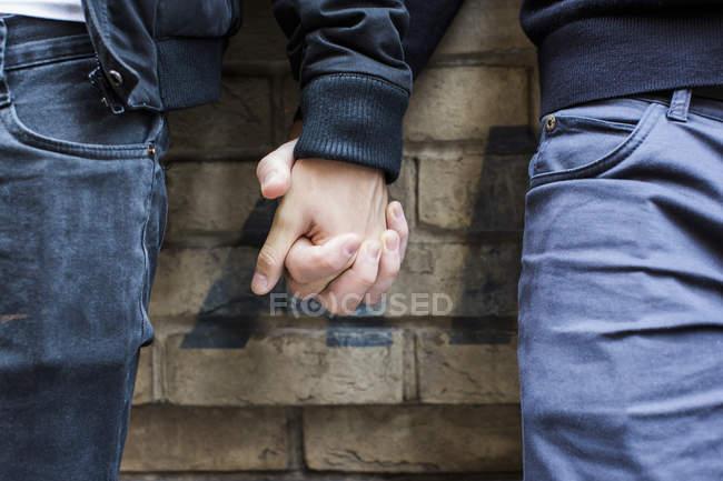 Primer plano de la pareja de homosexuales tomados de la mano - foto de stock