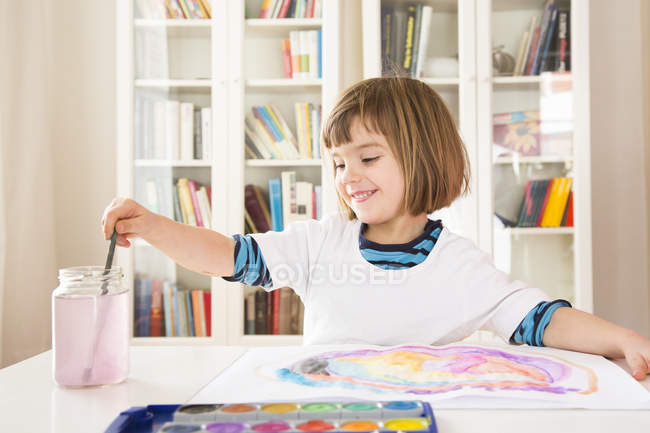 Portrait of smiling girl painting with watercolours — Stock Photo