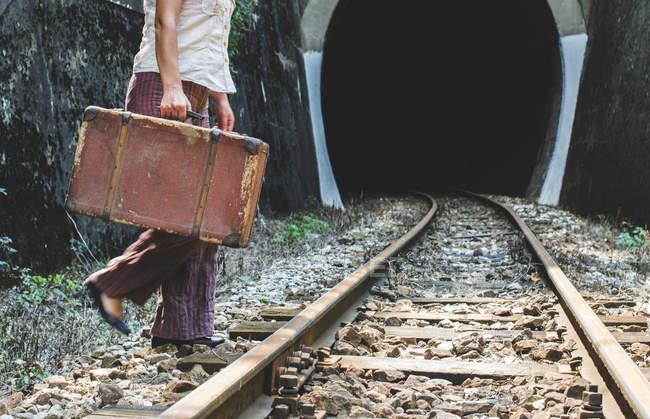 Mulher na estrada de ferro e túnel, mala na mão — Fotografia de Stock