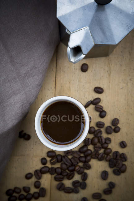 Cup of black coffee, cloth, espresso can and coffee beans on wood — Stock Photo