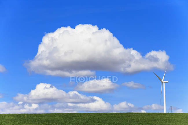 USA, Idaho, Palouse, Wind turbine on meadow and clouds in blue sky — Stock Photo