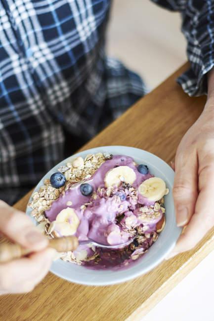 Uomo in pigiami mangiare muesli con yogurt di soia, mirtilli e banana in ciotola — Foto stock