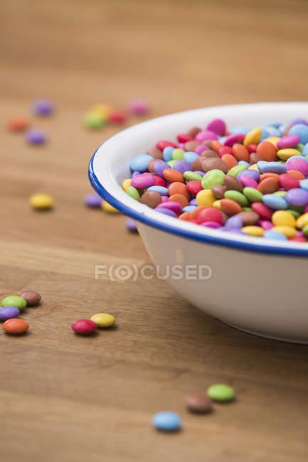 Tigela de botões de chocolate na superfície de madeira — Fotografia de Stock