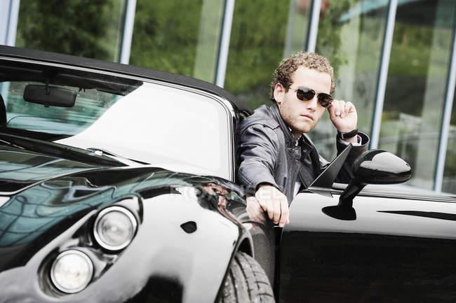 Giovane uomo con gli occhiali da sole seduto in auto sportiva nera — Foto stock