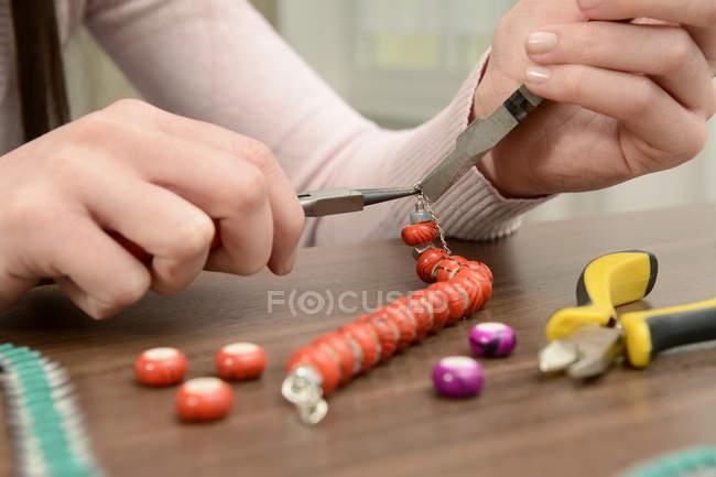 Молода жінка працює над саморобні браслет — стокове фото