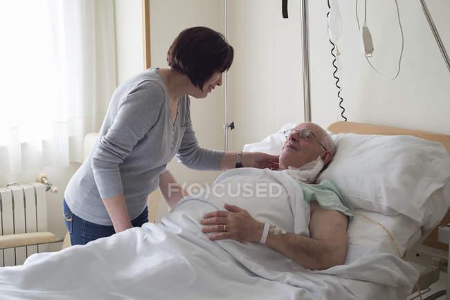 Mujer mayor que cuida de su marido en el hospital recuperándose después de la cirugía - foto de stock