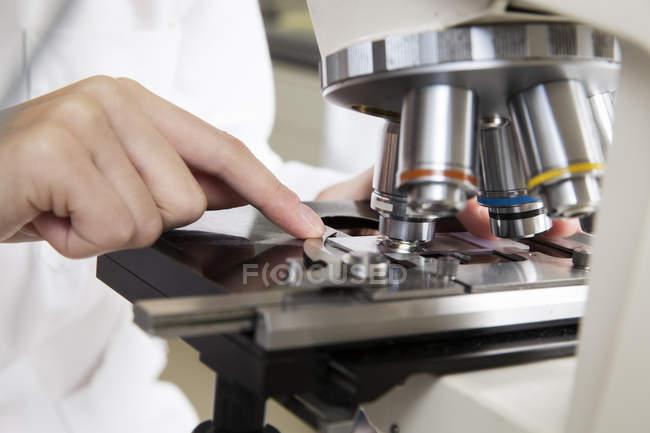 Vue recadrée d'une chercheuse travaillant au microscope — Photo de stock