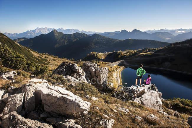 Pareja joven de Austria, Altenmarkt-Zauchensee, con bicicletas de montaña, descansando sobre roca en las montañas - foto de stock