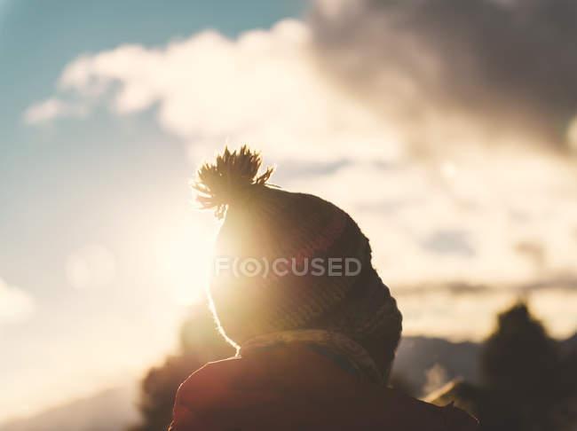 Homem de pé com chapéu de lã ao pôr do sol com céu nublado — Fotografia de Stock