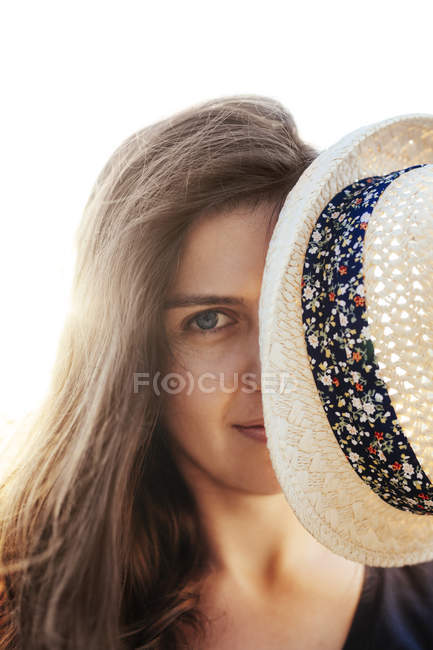 Woman hiding behind her summer hat — Stock Photo