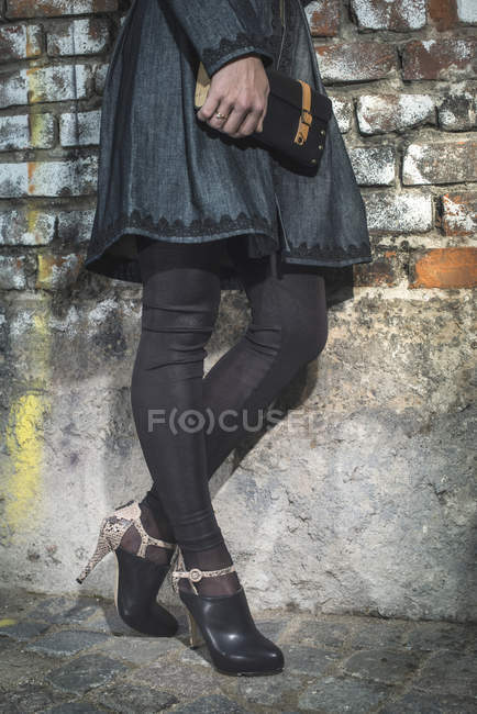Woman leaning on brick wall holding leather handbag — Stock Photo